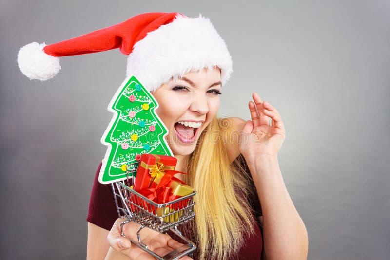 Mulher feliz que guarda o carrinho de compras com presentes do Natal foto de stock