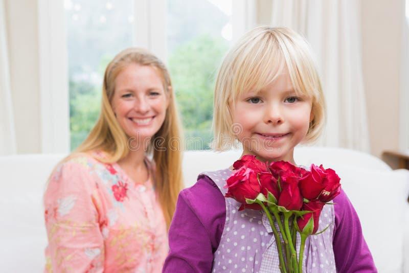 Mulher feliz que guarda rosas vermelhas com filha fotos de stock royalty free