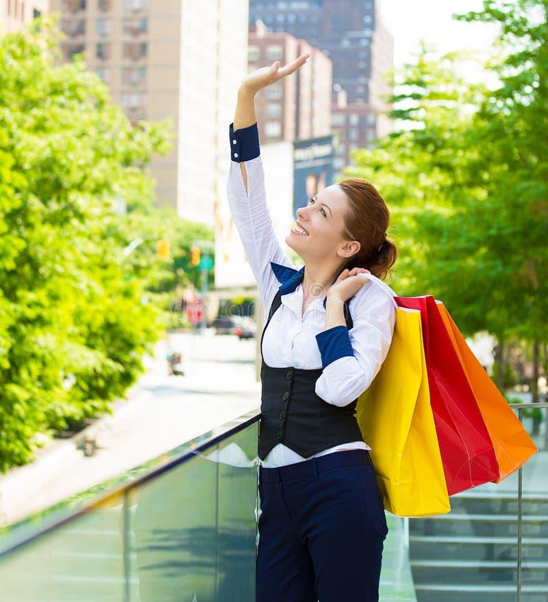 Mulher feliz que guarda sacos de compras e que sorri na alameda imagem de stock