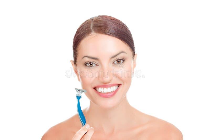 Mulher feliz que guarda sua lâmina de rapagem aproximadamente para barbear sua cara imagens de stock royalty free