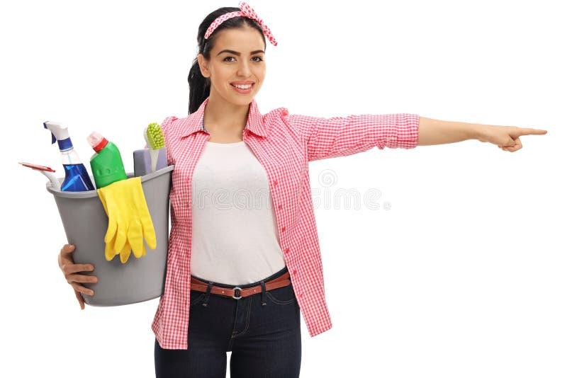 A mulher feliz que guarda uma cubeta encheu-se com os produtos de limpeza e o p fotos de stock