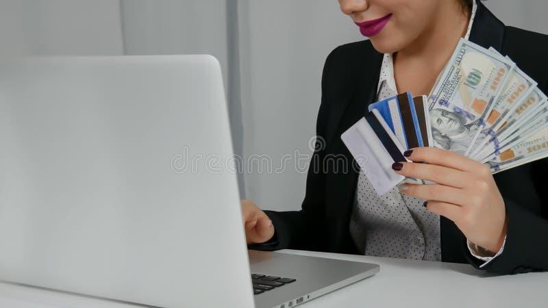 A mulher feliz que guardam dólares americanos e os cartões de crédito aproximam seu portátil foto de stock royalty free