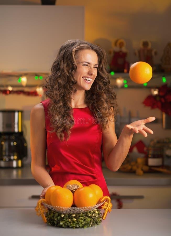 A mulher feliz que joga acima a laranja no Natal decorou a cozinha fotos de stock
