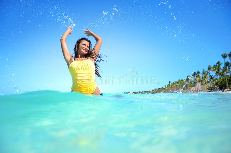 Mulher feliz que joga com água na praia exótica fotos de stock
