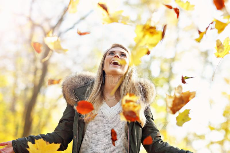 Mulher feliz que joga com folhas de outono fora foto de stock