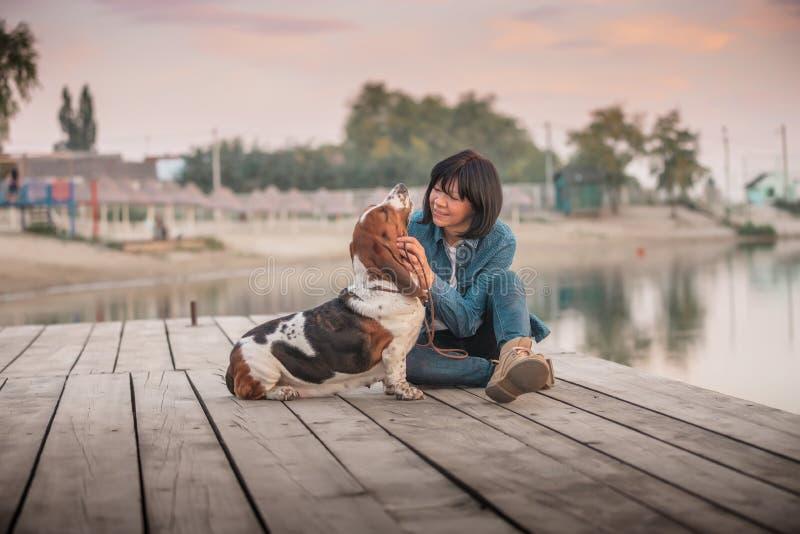 Mulher feliz que joga com seu cão pelo rio imagens de stock
