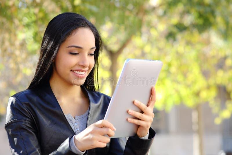 Mulher feliz que lê um leitor da tabuleta em um parque imagens de stock