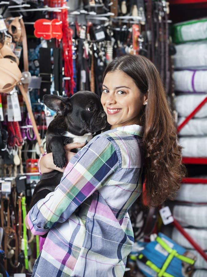 Mulher feliz que leva o buldogue francês na loja fotografia de stock