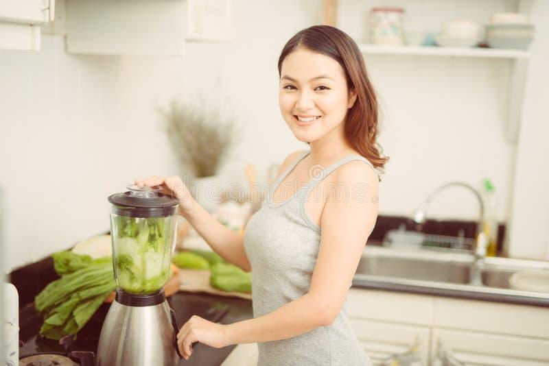 Mulher feliz que mistura vegetais verdes no misturador ao preparar o cocktail energ?tico imagem de stock