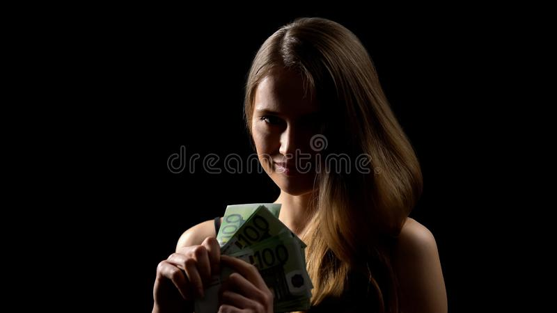 Mulher feliz que mostra cédulas dos euro contra o fundo preto, jackpot do casino fotografia de stock