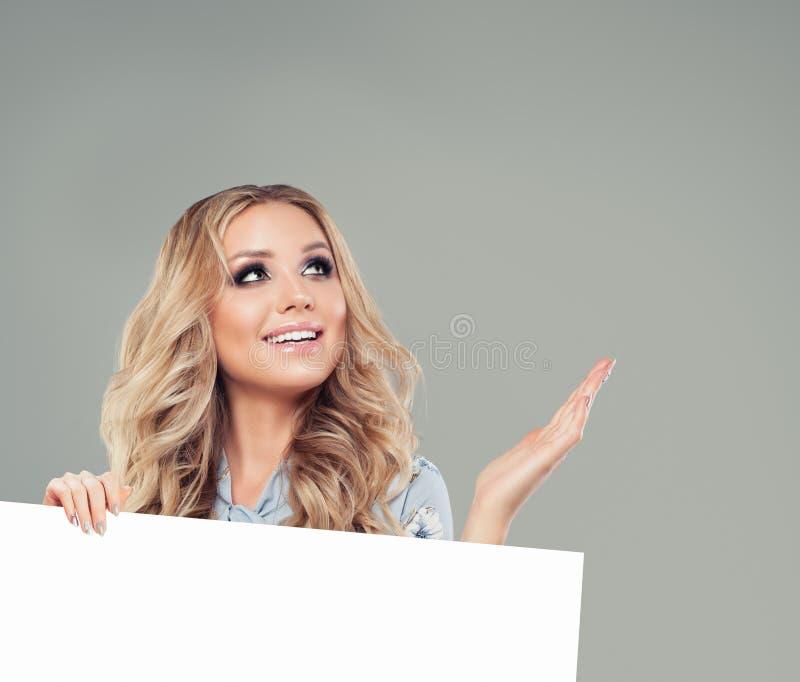 Mulher feliz que mostra a mão aberta vazia e que guarda a placa branca foto de stock