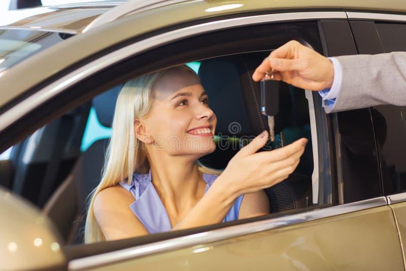 Mulher feliz que obtém a chave do carro na feira automóvel ou no salão de beleza fotos de stock