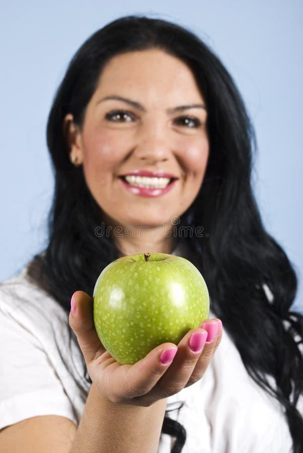 Mulher feliz que oferece uma maçã imagens de stock royalty free