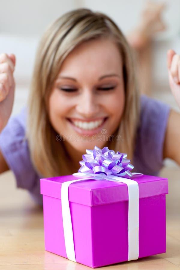 Mulher feliz que olha um presente que encontra-se no assoalho imagem de stock