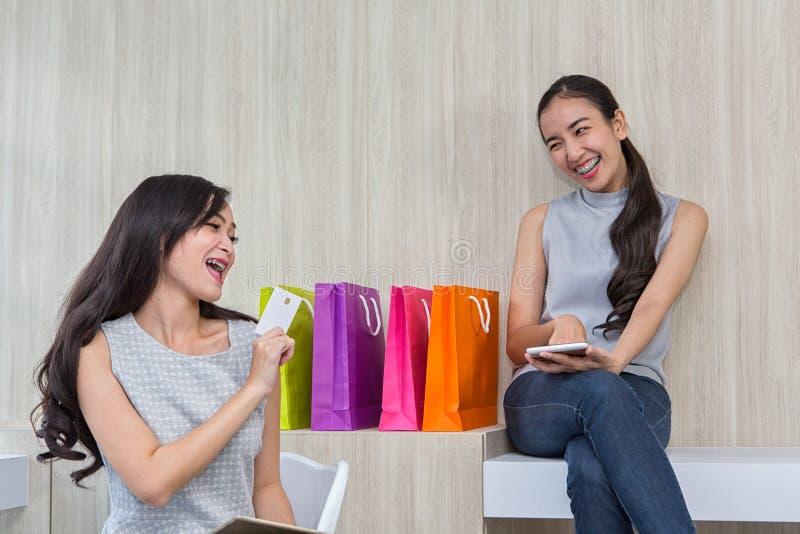 Mulher feliz que paga no café pelo cartão de crédito e pelo telefone esperto A mulher tomou um pagamento sem contato E imagens de stock royalty free