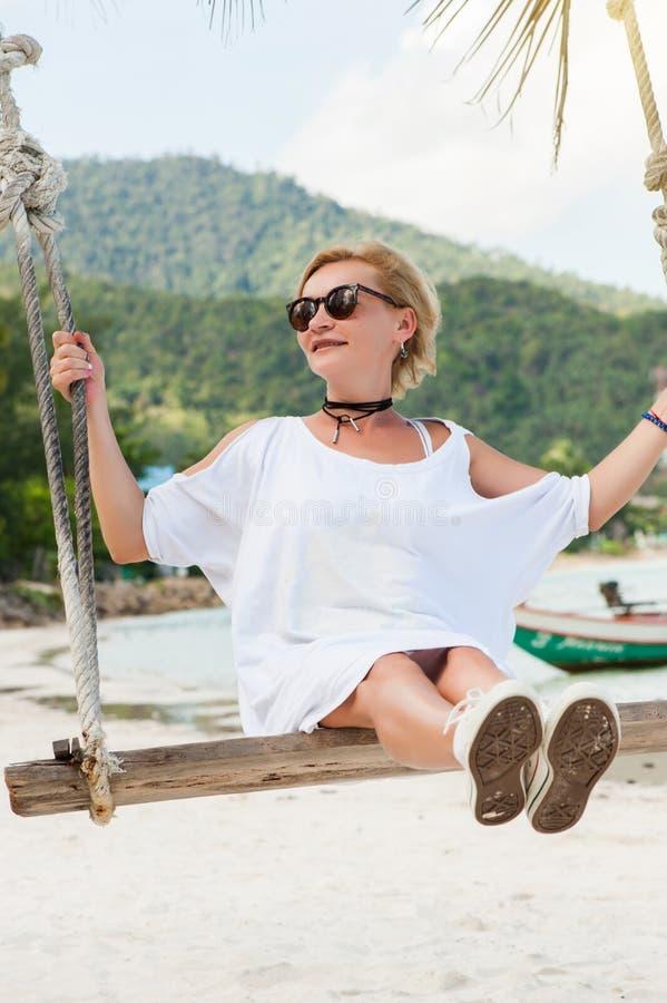 Mulher feliz que relaxa com balanço de suspensão na praia tropical imagem de stock royalty free