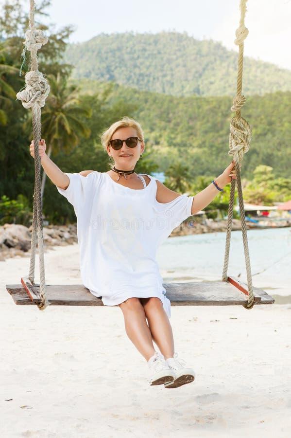 Mulher feliz que relaxa com balanço de suspensão na praia tropical foto de stock royalty free