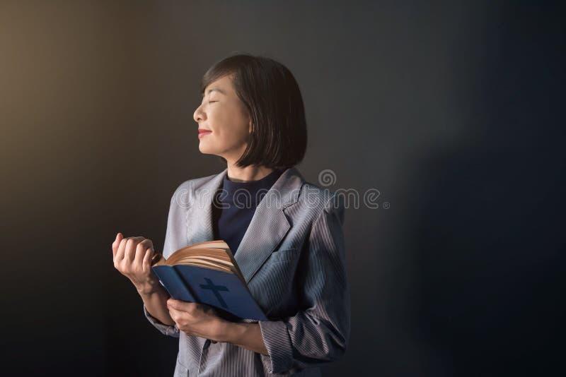 Mulher feliz que reza na sala escura, sorriso fêmea, olho fechado fotos de stock