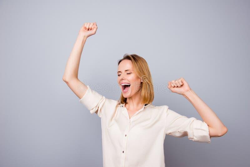 Mulher feliz que ri e que triunfa com os braços aumentados contra o gra fotografia de stock