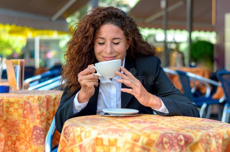 Mulher feliz que saborea o aroma de seu café imagens de stock royalty free