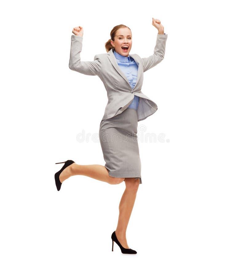 Mulher feliz que salta com mãos acima fotos de stock