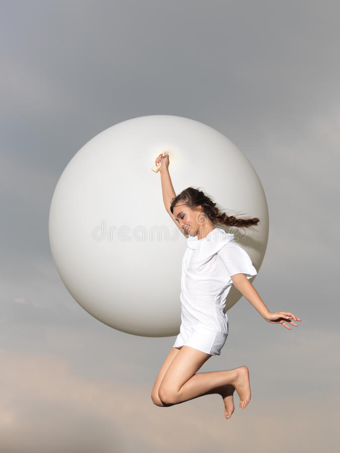 Mulher feliz que salta com o balão grande, branco foto de stock royalty free