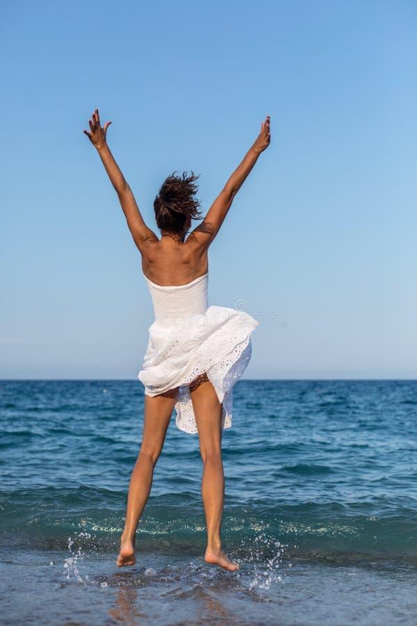 Mulher feliz que salta em uma costa de mar imagens de stock