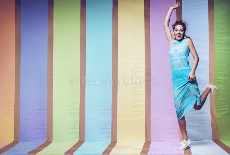 Mulher feliz que salta no vestido listrado azul fotografia de stock