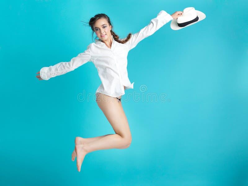 Mulher feliz que salta o chapéu azul do branco do fundo imagens de stock