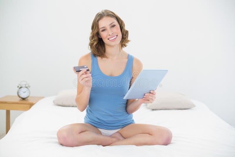 Mulher feliz que senta-se em sua cama usando sua tabuleta para compras ao domicílio foto de stock