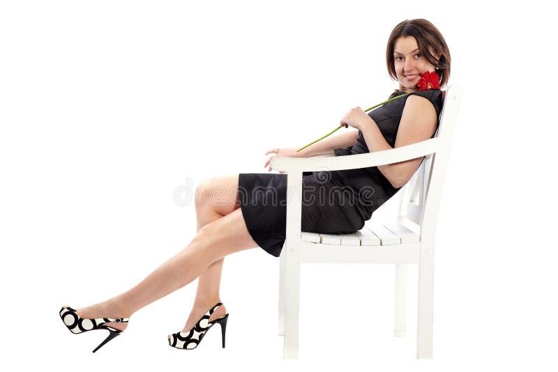 Mulher feliz que senta-se na cadeira de madeira, guardando uma flor e um d imagens de stock royalty free