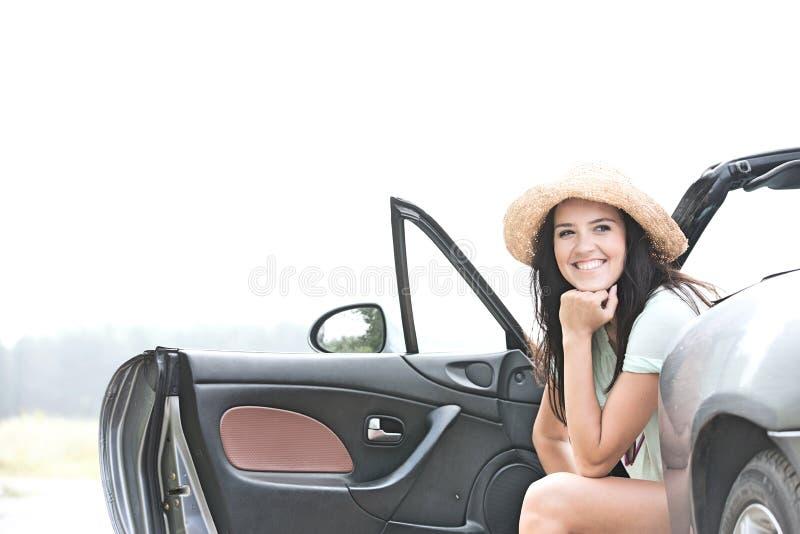 Mulher feliz que senta-se no convertible contra o céu claro fotos de stock royalty free