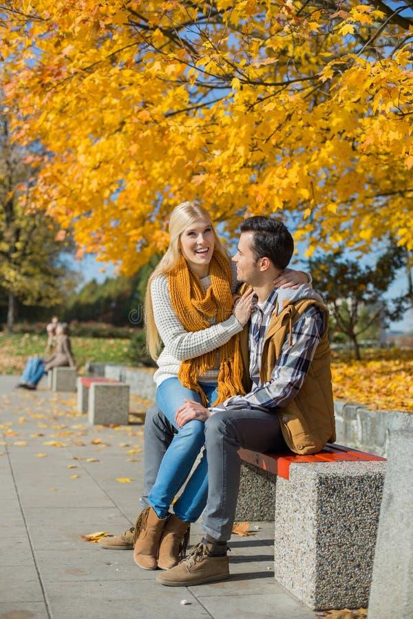 Mulher feliz que senta-se no regaço do homem no parque durante o outono imagem de stock royalty free