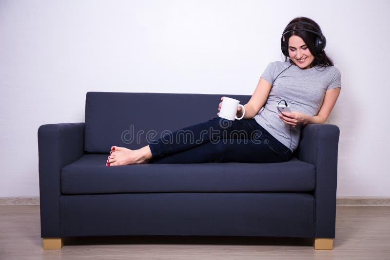 Mulher feliz que senta-se no sofá, música de escuta com telefone celular a foto de stock