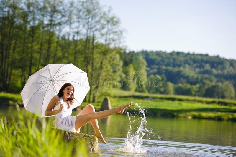 Mulher feliz que senta-se pelo lago que espirra a água imagens de stock royalty free