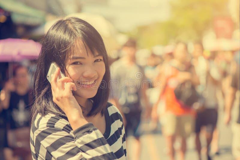 Mulher feliz que sorri e que anda na rua que fala um smartphone e que olha a câmera fotos de stock