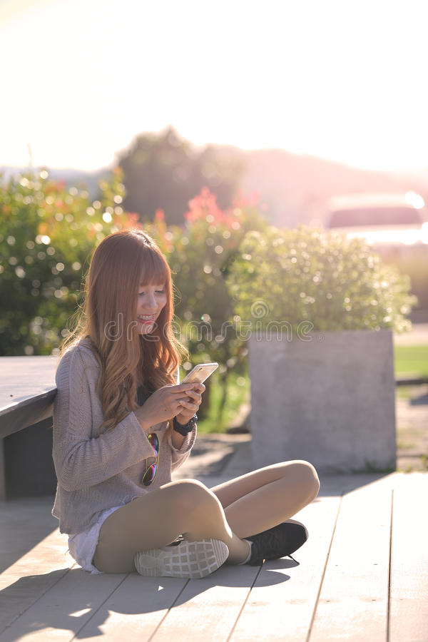 Mulher feliz que sorri e que usa um smartphone fotos de stock