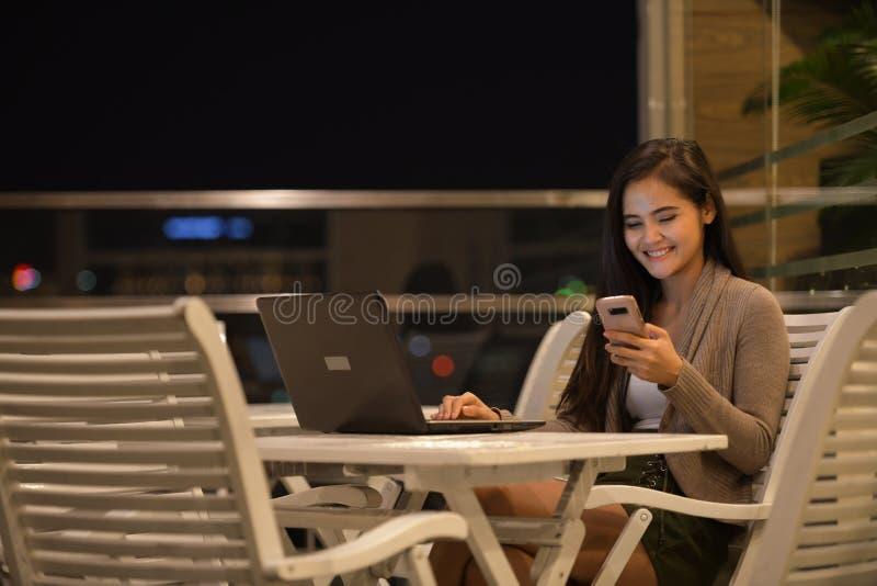 Mulher feliz que sorri e que usa o ar livre do telefone celular e do laptop na noite fotos de stock