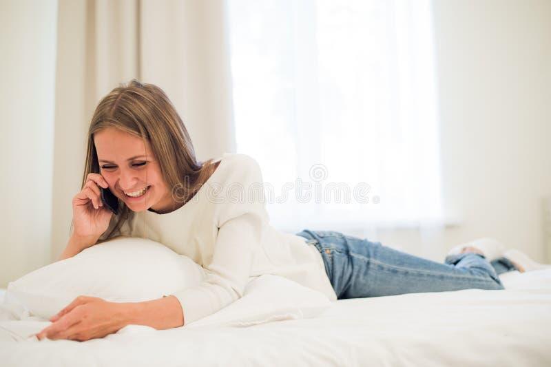 Mulher feliz que sorri no telefone que coloca na cama fotografia de stock