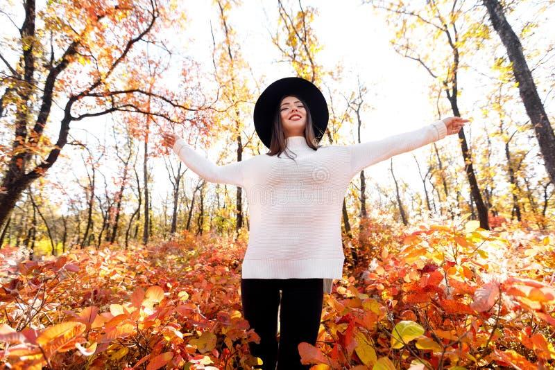Mulher feliz que tem o divertimento no parque no dia ensolarado do outono imagem de stock