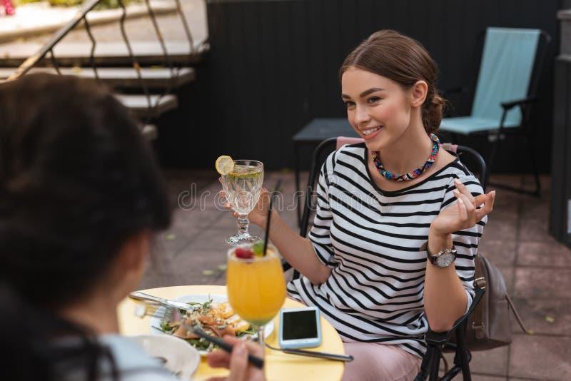 Mulher feliz que tem o jantar com seu melhor amigo no restaurante novo fotos de stock