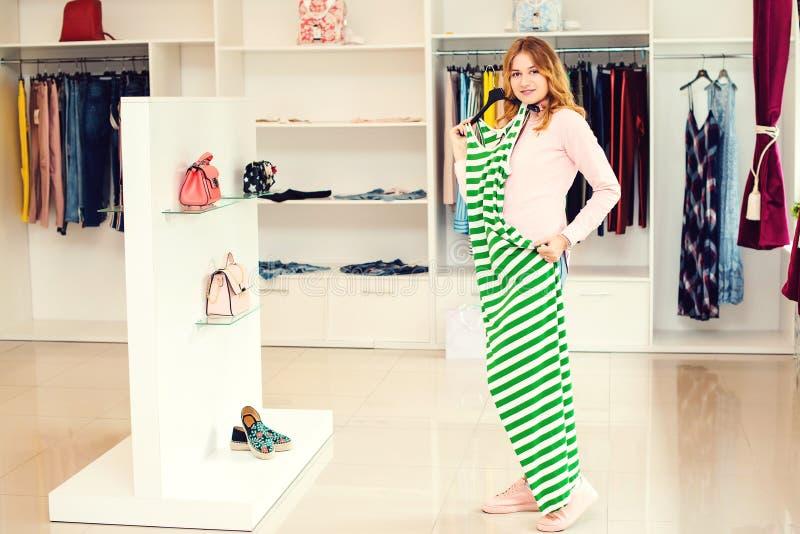 Mulher feliz que tenta no vestido novo na sala de exposições Conceito da forma e da escolha Compra, forma, roupa, estilo e concei imagem de stock