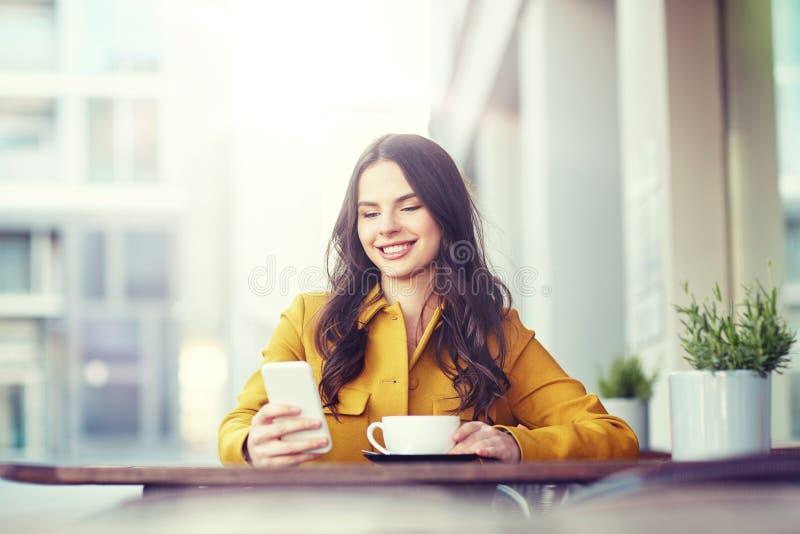 Mulher feliz que texting no smartphone no café da cidade fotografia de stock