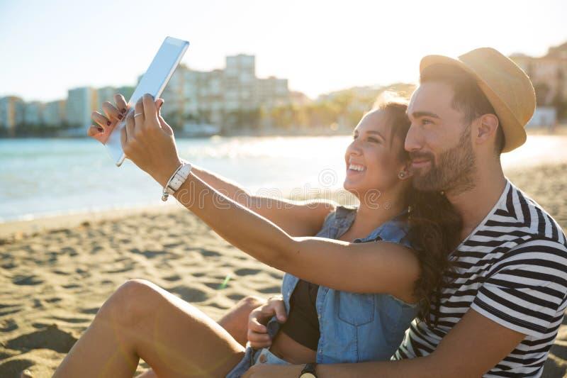 Mulher feliz que toma o selfie com seu noivo pela tabuleta na praia imagens de stock royalty free