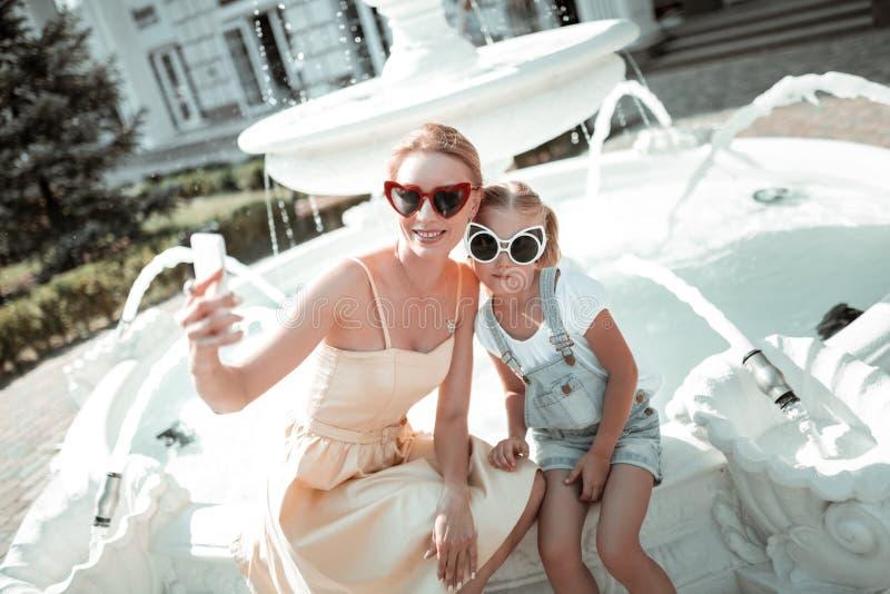 Mulher feliz que toma um selfie com sua filha fotos de stock royalty free