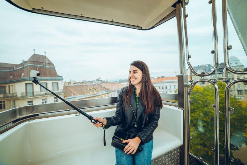Mulher feliz que toma um selfie na roda de ferris imagens de stock royalty free