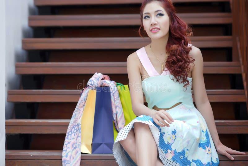 Mulher feliz que toma uma ruptura com sacos de compras ao sentar-se em t fotos de stock royalty free