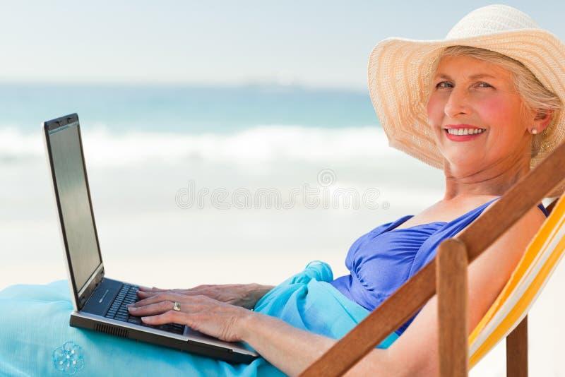 Mulher feliz que trabalha em seu portátil imagem de stock