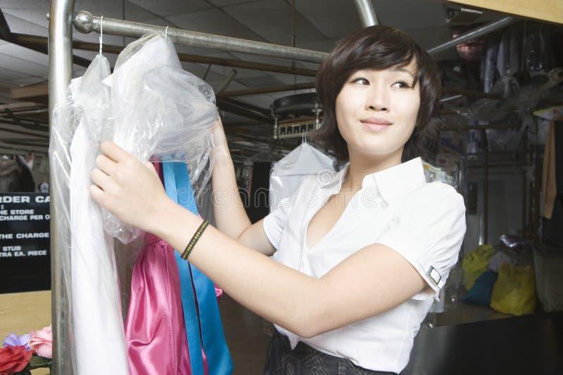 Mulher feliz que trabalha na lavanderia imagens de stock