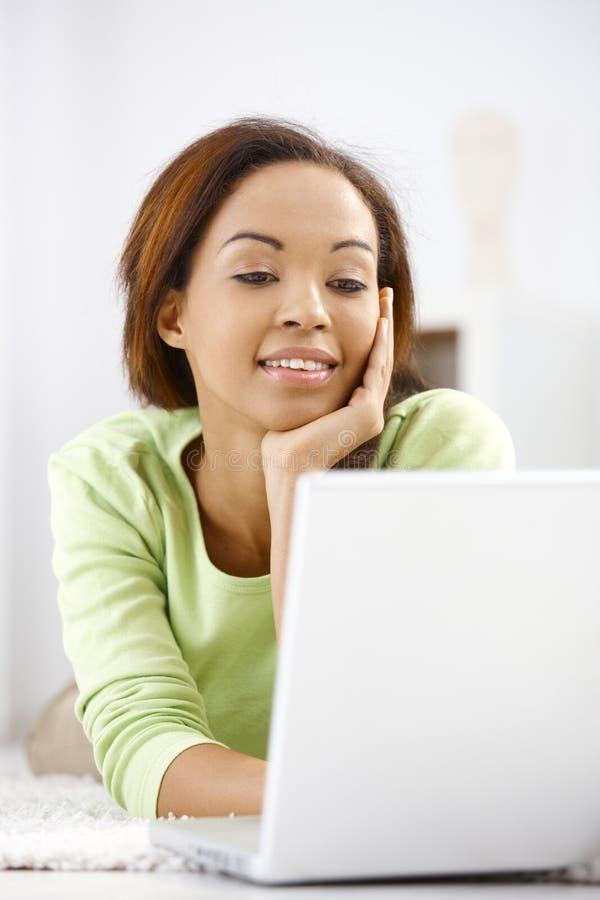 Mulher feliz que usa o computador imagem de stock royalty free